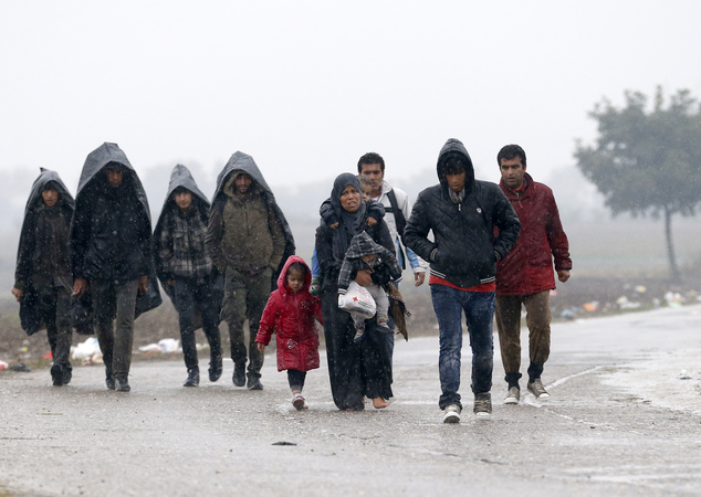 A group of migrants walk on the road near a border line between Serbia and Croatia, near the village of Berkasovo, Serbia, Monday, Oct. 19, 2015. Tension was building among thousands of migrants as they remained stranded in fog and cold weather in the Balkans on Sunday in their quest to reach a better life in Western Europe, two days after Hungary closed its border with Croatia and the flow of people was redirected to a much slower route via Slovenia. (AP Photo/Darko Vojinovic)